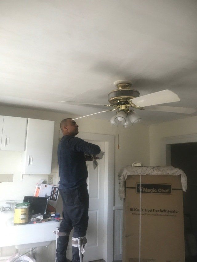 Man doing drywall repairs around ceiling fan